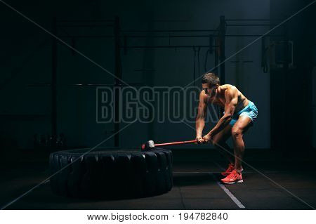 Athletic young man hitting big tire with hummer. Male adult working out in gym. Weightlifting or functional training. Sports and fitness concept.