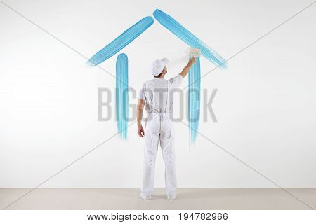 home service concept. painter man with brush drawing a blue house isolated on the blank white wall