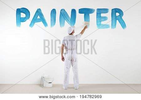 painter man with paint brush drawing a blue painter text isolated on the blank white wall