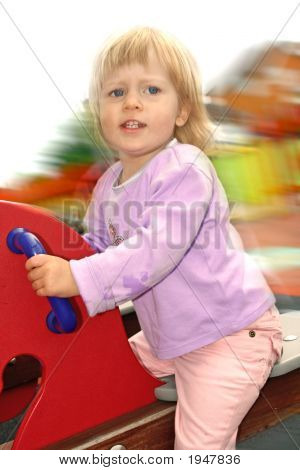 Toddler On Wooden Pony See Saw In Playground