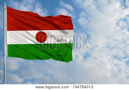 National flag of Niger on a flagpole in front of blue sky.