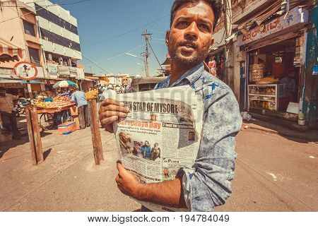 MYSORE, INDIA - FEB 16, 2017: Man selling newspaper Star Of Mysore on colorful street with market stalls and stores on February 16, 2017. Mysore of Karnataka has a population of 900000