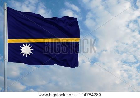 National flag of Nauru on a flagpole in front of blue sky.