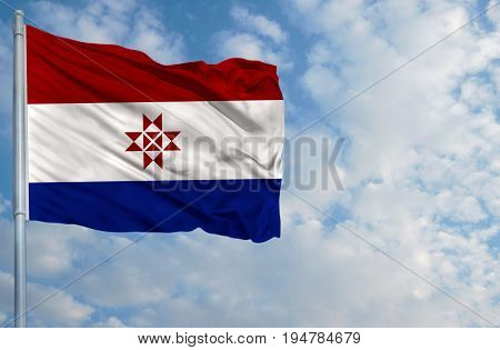 National flag of Mordovia on a flagpole in front of blue sky.
