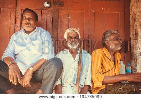 MYSORE, INDIA - FEB 16, 2017: Three elderly indian man sitting outdoor past wooden door of city market on February 16, 2017. Mysore of Karnataka has a population of 900000
