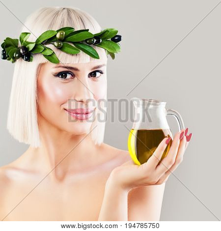 Beautiful Woman with Green Olive Leaves Wreath and Glass Bottle of Organic Olive Oil. Healthy Eating and Mediterranean Diet Concept