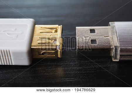Silvery usb flash drive on a black desk and usb cable for connection close-up. A metal flash drive for storing memory on a dark background with hard light. Cable for data transmission. Long cable. Cable for connecting with flash drive. Gray flash drive on