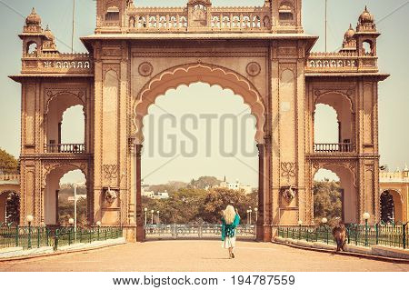 Woman walking to the famous landmark - Historical gates of the royal Palace of Mysore in Karnataka, India