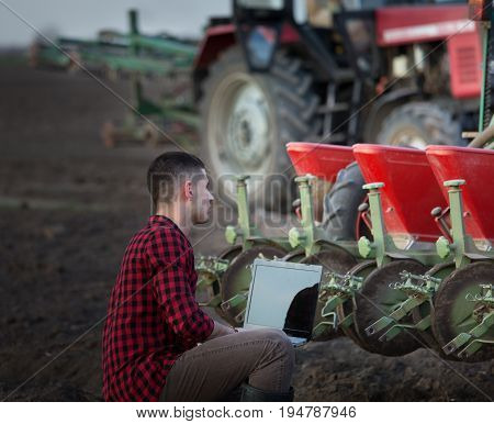 Farmer With Laptop And Tractors