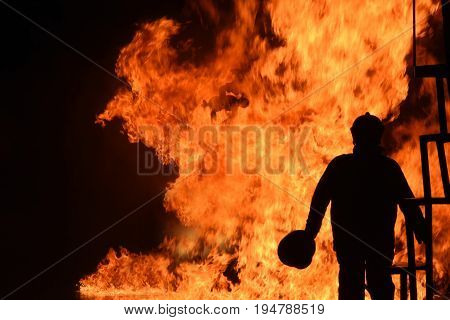 Silhouette of Firemen fighting a raging fire with huge flames of burning timber .