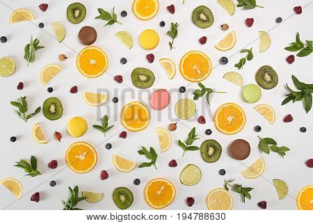Flat Lay Still Life With Macarons, Berries, Mint, Lemon, Orange Fruit, Lime, Kiwi