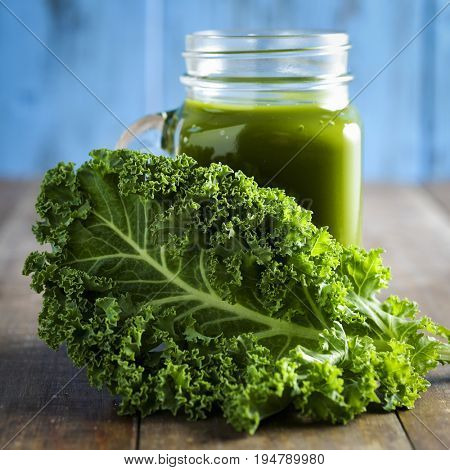 a kale smoothie served in a mason jar and a leaf of kale, on a rustic wooden table