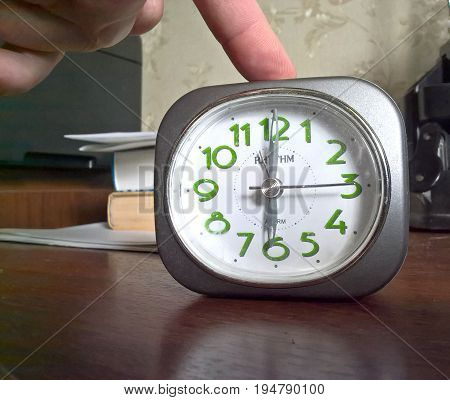 Hand early in the morning turns off ringing alarm clock