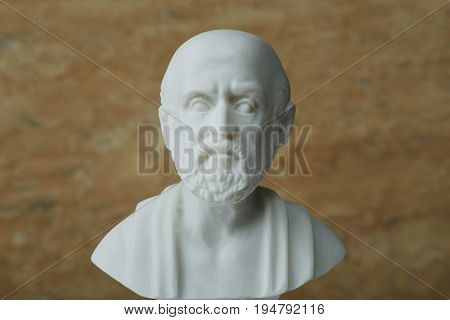Statue of Hippocrates, ancient Greek physician on brown background.