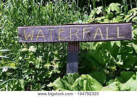 A wood sign for the trail leading to the waterfall