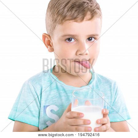 Lovely little boy in blue T-shirt is holding milk and showing the tongue, isolated on a white background. A pretty little boy  with blonde hair is holding a glass of milk and shows the tongue.