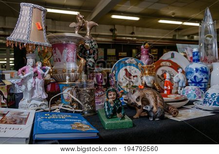 Moscow, Russia - March 19, 2017: Showcase with vintage figures and dishes made of porcelain and ceramics on the flea market. Antique fair is popular with collectors and antiques fans.
