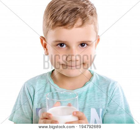 Handsome little boy with likable blonde hair in blue T-shirt holds a glass of milk and looks happy, isolated on a white background. Close-up portrait of a cute little kid holds milk and pretty smiles