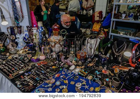 Moscow, Russia - March 19, 2017: Shop with cheap women's jewelry, beads, pendants, earrings and bijou at the flea market. An elderly gray-haired merchant in the background is waiting for customers.