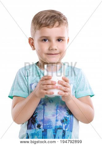 Close-up portrait of a little cheerful child with dimples on his cheeks holding a glass of tasty milk isolated on a white background.  A pretty boy is wearing a blue T-shirt and holds a glass of milk.