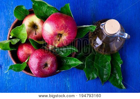 Apple Cider Vinegar In Glass Bottle On Blue Background. Red Apples In Brown Bowl. Top View.