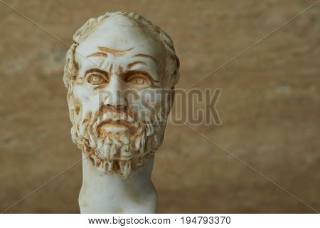 Statue of Demokritus, ancient Greek philosopher on brown background.