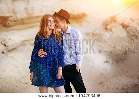 An Attractive Man Is Hugging And Kissing An Beautiful Woman In A Blue Dress In The Middle Of A Sandy