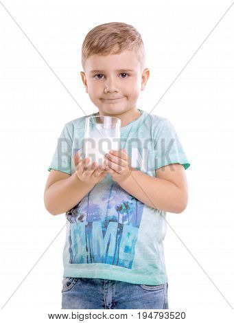 Handsome little boy with likable blonde hair in blue T-shirt holds a glass full of milk and looks happy, isolated on a white background.  Beautiful little kid holds milk and pretty smiles.