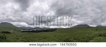 A panoramic view over the rolling hills of Scottish Highlands with Loch Tulla nestling within a surrounding forest.