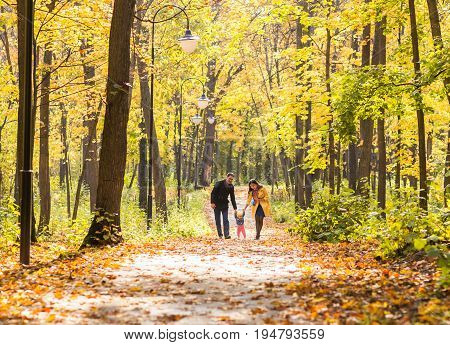 Happy young family in the autumn park outdoors on a sunny day. Mother, father and their little baby girl are walking in the park. Love and family concept