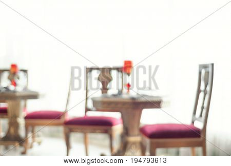 Classic style chairs and coffee table in the brightly lit room. An abstract interior background with lens blur effect.