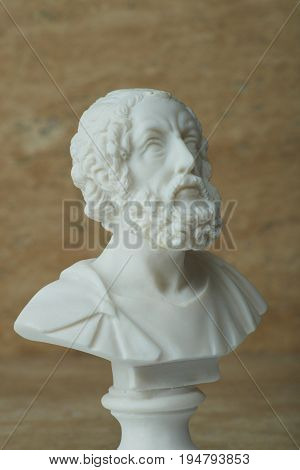 Statue of Homer, ancient Greek poet on brown background.
