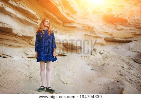 Beautiful Redheaded Girl Standing In A Blue Dress In The Middle Of A Sand Quarry
