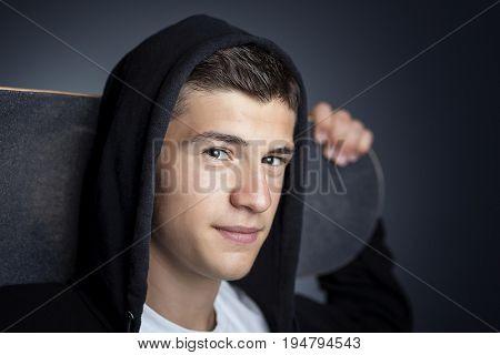 portrait of smiling boy with skateboard