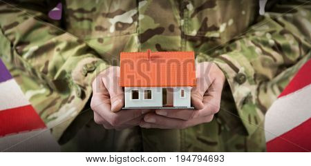 Mid section of soldier holding model home against waving flag of america