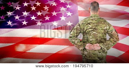 Rear view of soldier standing with his hands behind back against close-up of american flag