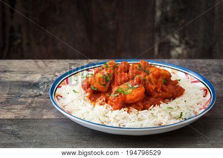 Chicken tikka masala with basmati rice on wooden table