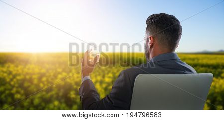 Rear view of businessman holding whisky glass against scenic view of beautiful mustard field