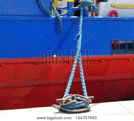 Thick braids of white rope tied to a mooring at a harbor Thick ropes used to secure boats and sea vessels to the dock