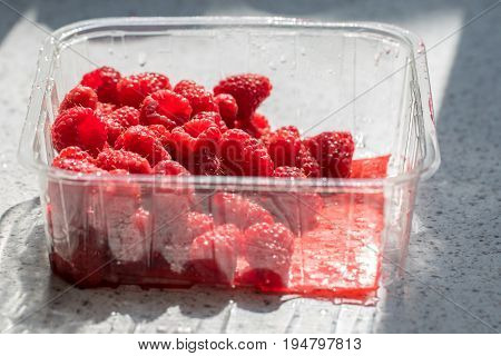 Raspberries in plastic supermarket tub packaging. Healthy ripe red organic fruit in shop bought recyclable container on kitchen worktop.