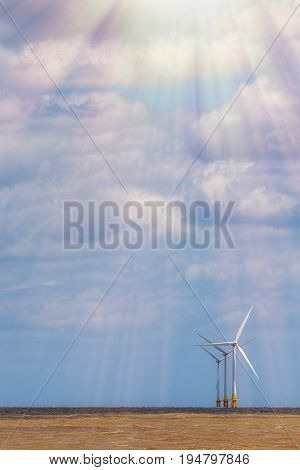 Clean energy. Future of sustainable resources electricity production. Offshore wind turbines in bright suinshine. Beautiful sky with natural copy space.