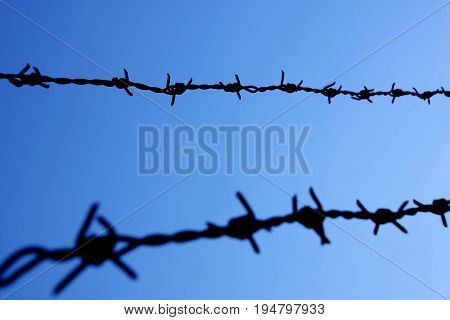 Barbed wire against blue sky selective focus.