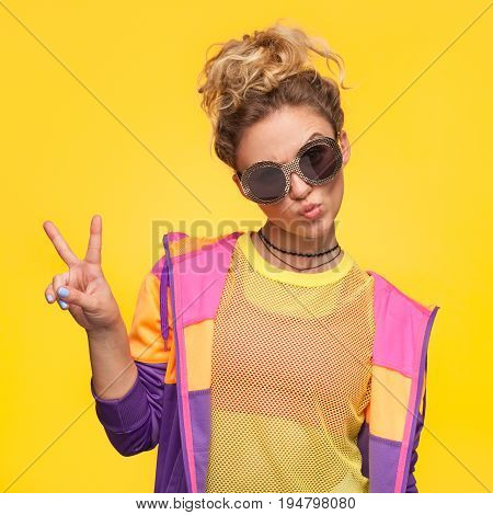 Blonde hipster girl with hair bun wearing colorful jacket, yellow sheer shirt grimacing making v-sign.