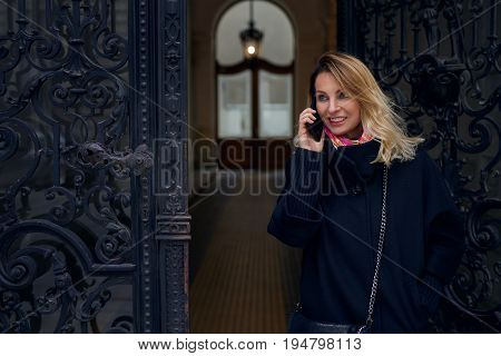 Stylish blond woman standing in an ornate historic doorway with classical carvings talking on her mobile phone with a smile of pleasure