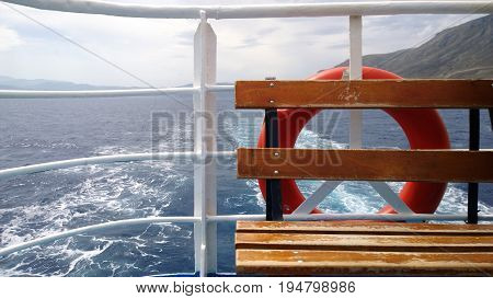 Safety on a passenger vessel: a bench and a lifeline. Visible trace of the sailing ship and mountains in the distance