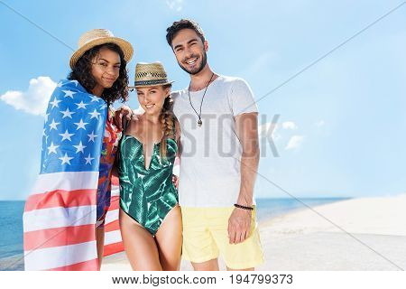 Portrait of two young jolly women in summer hats and one bearded guy standing on river shore. Mulatto girl is wrapping up in american flag pareu. Copy space in right side