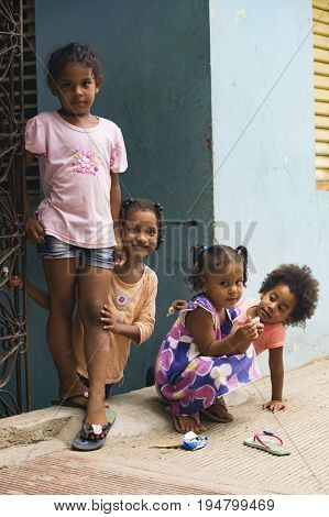 LAS TERRENAS, DOMINICAN REPUBLIC - SEPTEMBER 28, 2016: four unidentified girls posing near house door. In the Dominican Republic, more than 40% of the population lives below the poverty line.