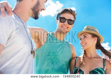 Happy young two men and jolly girl are standing and hugging by shoulders each other. Sunny sky on background