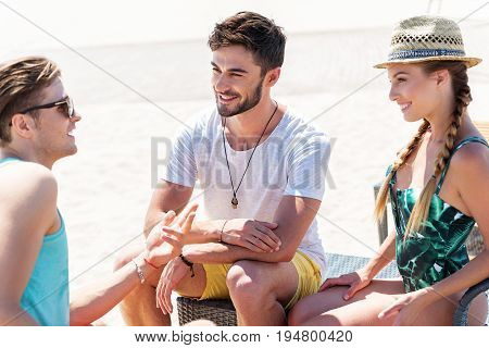 Two young happy men and woman in swimsuit and straw hat are sitting on beach on sunlounger. They are discussing something with joy