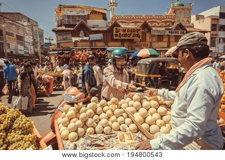 MYSORE, INDIA - FEB 16, 2017: Driver in helmet buying fresh fruits and oranges on outdoor marketplace with many customers on asian street on February 16, 2017. Mysore of Karnataka has population of 900000